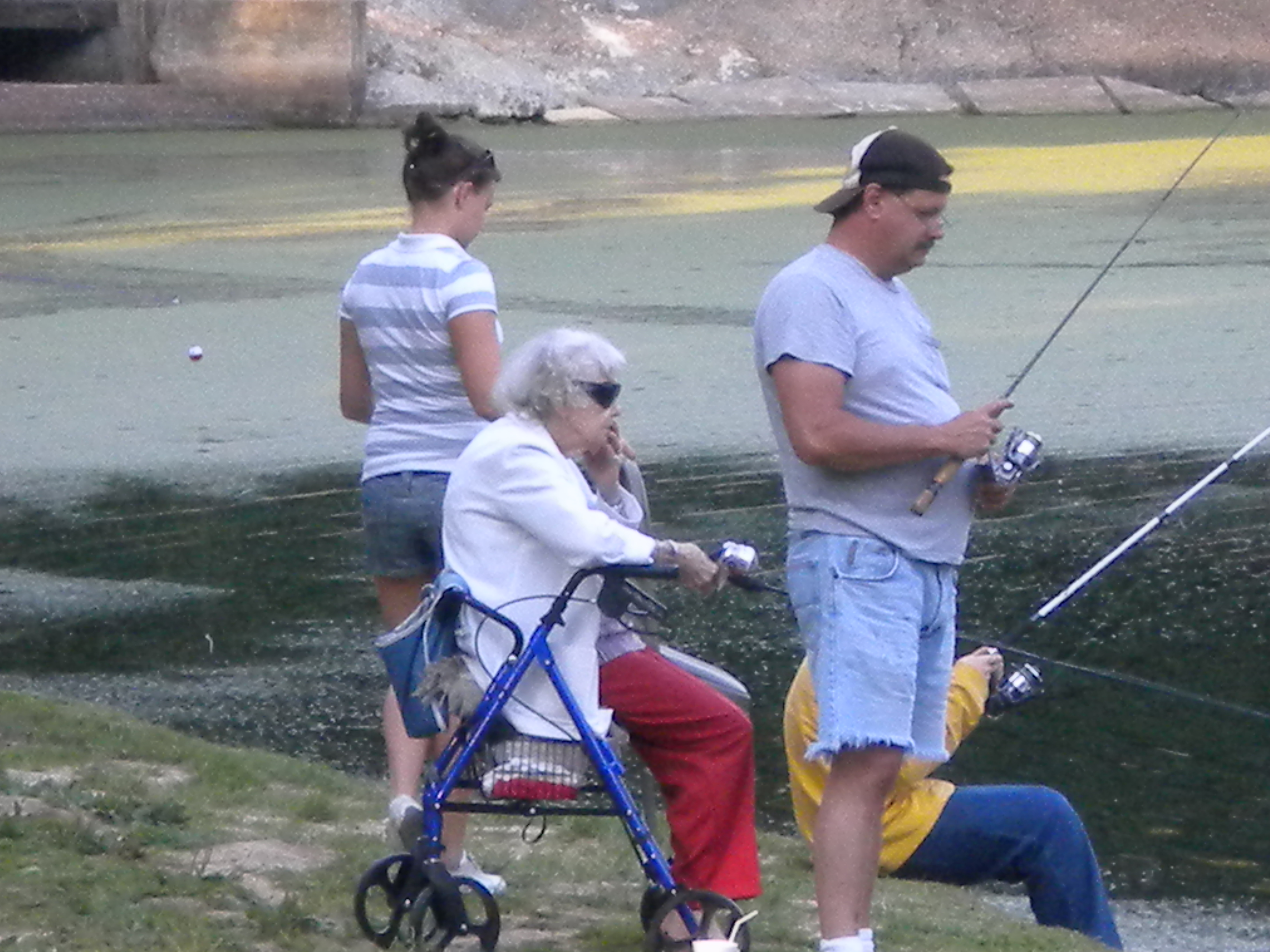 An elderly woman, a young girl, a middle aged man, and a young person fishing off the shore.